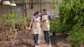 Ο άνδρας γεωπόνων με την ταμπλέτα διευθύνει την επιθεώρηση της ανάπτυξης των εγκαταστάσεων στο θερμοκήπιο με τον κηπουρό γυναικών φιλμ μικρού μήκους