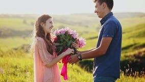 Ο άνδρας δίνει μια δέσμη των λουλουδιών σε μια γυναίκα Το νέο ζεύγος έχει μια ημερομηνία στο ηλιοβασίλεμα πίσω από την πόλη απόθεμα βίντεο