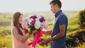 Ο άνδρας δίνει μια δέσμη των λουλουδιών σε μια γυναίκα Το νέο ζεύγος έχει μια ημερομηνία στο ηλιοβασίλεμα στο πάρκο απόθεμα βίντεο