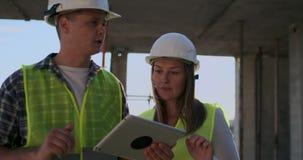 Ο άνδρας εργατών οικοδομών και η γυναίκα αρχιτεκτόνων σε ένα κράνος, συζητούν το σχέδιο της κατασκευής του σπιτιού, λένε ο ένας τ απόθεμα βίντεο