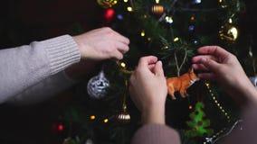 Ο άνδρας και η γυναίκα διακοσμούν το χριστουγεννιάτικο δέντρο σε σε αργή κίνηση απόθεμα βίντεο