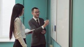 Ο άνδρας και η γυναίκα διευθύνουν μια επιχειρησιακή συνεδρίαση whiteboard πλησίον απόθεμα βίντεο