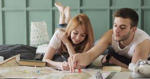 Ο άνδρας και η γυναίκα ζεύγους προγραμματίζουν τις διακοπές χρησιμοποιώντας έναν παγκόσμιο χάρτη Γυναίκα που υπογραμμίζει τα σημε απόθεμα βίντεο