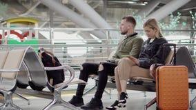 Ο άνδρας και η γυναίκα κάθονται στην αίθουσα αναμονής στον αερολιμένα, οι βαλίτσες είναι πλησίον φιλμ μικρού μήκους