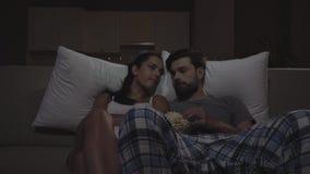 Ο άνδρας και η γυναίκα κάθονται στο σκοτάδι στον κινηματογράφο καναπέδων και προσοχής Τρώνε popcorn Ενάρξεις κοριτσιών στην πτώση φιλμ μικρού μήκους