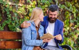 Ο άνδρας και η γυναίκα κάθονται το πάρκο πάγκων Διαβάστε το ίδιο βιβλίο από κοινού Ενδιαφερόμενη ζεύγος λογοτεχνία Κοινό ενδιαφέρ στοκ εικόνα