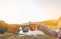 ο άνδρας και η γυναίκα καφές έχουν μιας συνεδρίασης και των γυαλιών στη φύση Στοκ Εικόνες