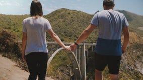Ο άνδρας και η γυναίκα κινηματογραφήσεων σε πρώτο πλάνο περπατούν μαζί να κρατήσουν τα χέρια στην επική όμορφη άποψη της γέφυρας  φιλμ μικρού μήκους