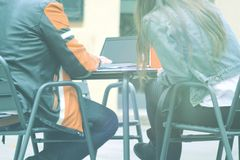 Ο άνδρας και η γυναίκα κοιτάζουν αδιάκριτα με ένα lap-top με τη συνεδρίαση σύνδεσης wifi σε έναν καφέ Έννοια τηλεργασίας και κενό Στοκ Φωτογραφία