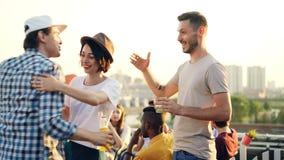Ο άνδρας και η γυναίκα κουβεντιάζουν στο υπαίθριο κόμμα που χαιρετά έπειτα το φίλο τους hipster που αγκαλιάζει, χέρια τινάγματος  απόθεμα βίντεο