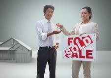 Ο άνδρας και η γυναίκα με για το σημάδι και τα κλειδιά πώλησης με το σπίτι διαμορφώνουν μπροστά από το σύντομο χρονογράφημα Στοκ Εικόνα