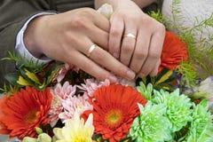 Ο άνδρας και η γυναίκα παραδίδουν τα γαμήλια δαχτυλίδια Στοκ Εικόνα