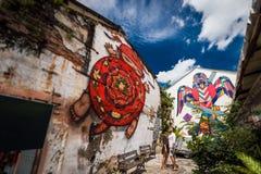 Ο άνδρας και η γυναίκα περπατούν γύρω από την παλαιά πόλη και εξετάζουν τα γκράφιτι οδών στοκ φωτογραφίες