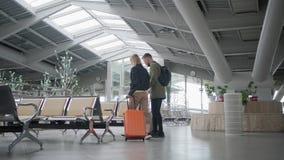 Ο άνδρας και η γυναίκα περπατούν μέσω της αίθουσας αναμονής του σταθμού, πίσω άποψη απόθεμα βίντεο