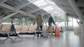 Ο άνδρας και η γυναίκα περπατούν μέσω του σαλονιού αναχώρησης με τις βαλίτσες και το κάθισμα απόθεμα βίντεο