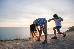 Ο άνδρας και η γυναίκα που έχουν τη διασκέδαση στο βουνό με τη λήψη άποψης παραλιών αστεία θέτουν Ηλιοβασίλεμα το βράδυ Στοκ Φωτογραφία