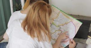 Ο άνδρας και η γυναίκα προγραμματίζουν τη διαδρομή ταξιδιού από το ταξίδι αυτοκινήτων χρησιμοποιώντας έναν χάρτη απόθεμα βίντεο