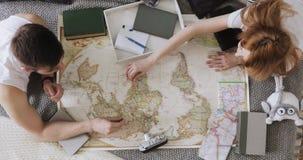Ο άνδρας και η γυναίκα προγραμματίζουν τις διακοπές χρησιμοποιώντας έναν παγκόσμιο χάρτη και άλλα εξαρτήματα ταξιδιού απόθεμα βίντεο