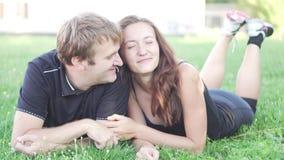 Ο άνδρας και μια γυναίκα βρίσκονται στη χλόη μετά από μια περίοδο αθλητικής άσκησης φιλμ μικρού μήκους
