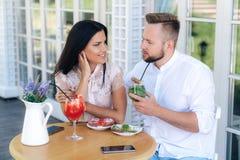 Ο άνδρας και μια γυναίκα κάθονται σε έναν καφέ, εξετάζουν ο ένας τον άλλον στοργικά, τρώνε τα εύγευστα επιδόρπια και πίνουν τα κο στοκ εικόνες