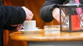 Ο άνδρας και μια γυναίκα πίνουν τον καφέ σε έναν καφέ οδών Ένα άτομο ανακατώνει ένα φλιτζάνι του καφέ με ένα κουταλάκι του γλυκού φιλμ μικρού μήκους