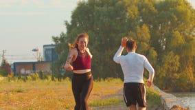 Ο άνδρας και μια γυναίκα τρέχουν ο ένας στον άλλο κατά μήκος της προκυμαίας και χτυπούν τα χέρια τους απόθεμα βίντεο