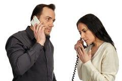 Ο άνδρας με ένα κινητό τηλέφωνο επικοινωνεί με τη γυναίκα με ένα εκλεκτής ποιότητας π Στοκ Φωτογραφία