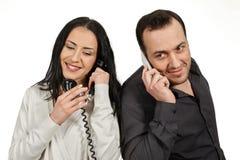 Ο άνδρας με ένα κινητό τηλέφωνο επικοινωνεί με τη γυναίκα με ένα εκλεκτής ποιότητας π Στοκ Εικόνα
