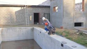 Ο άνδρας οικοδόμων και η γυναίκα επιθεωρητών σε ένα κράνος συζητούν τα σπίτια οικοδόμησης με μια λίμνη απόθεμα βίντεο