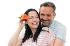Ο άνδρας που αγκαλιάζει τη γυναίκα με αυξήθηκε πίσω από το αυτί στοκ εικόνες