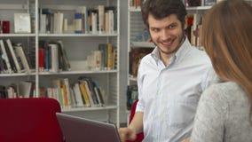 Ο άνδρας σπουδαστής παρουσιάζει στο θηλυκό συμμαθητή του κάτι στο lap-top στη βιβλιοθήκη στοκ εικόνα με δικαίωμα ελεύθερης χρήσης