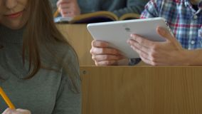 Ο άνδρας σπουδαστής παρουσιάζει στο συμμαθητή του κάτι στην ταμπλέτα στοκ εικόνες