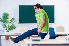 Ο άνδρας σπουδαστής που πάσχει από την ώθηση στην τάξη στοκ εικόνα με δικαίωμα ελεύθερης χρήσης