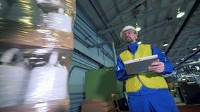 Ο άνδρας υπάλληλος με μια ταμπλέτα παρατηρεί το περιστρεφόμενο πακέτο των πλαστικών μεταλλικών κουτιών φιλμ μικρού μήκους
