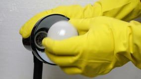 Ο άνθρωπος παραδίδει το κίτρινο λαστιχένιο γάντι ξεβιδώνει τη χαλασμένη λάμπα φωτός απόθεμα βίντεο