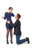 Ο άνδρας γονατίζει στη νέα γυναίκα, που λυπάται στοκ εικόνες