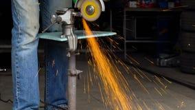Ο άνδρας εργαζόμενος με τη γωνιακή αλέθοντας μηχανή κόβει το μέταλλο φιλμ μικρού μήκους