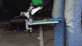 Ο άνδρας εργαζόμενος με τη γωνιακή αλέθοντας μηχανή κόβει το μέταλλο κίνηση αργή φιλμ μικρού μήκους