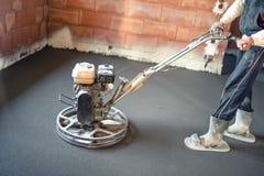 Ο άνδρας εργαζόμενος με τη δύναμη trowel σχεδιάζει το τσιμεντένιο πάτωμα λήξης, ομαλή συγκεκριμένη επιφάνεια Στοκ Φωτογραφίες