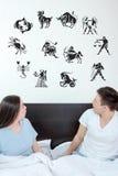 Ο άνδρας και η έκπληκτη γυναίκα στην κρεβατοκάμαρα περιέβαλαν να εξετάσουν επάνω το horo Στοκ φωτογραφίες με δικαίωμα ελεύθερης χρήσης