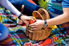 Ο άνδρας και η γυναίκα άρπαξαν για ένα μήλο σε ένα πικ-νίκ Στοκ Εικόνες