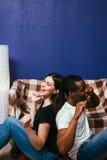 Ο άνδρας και η γυναίκα απολαμβάνουν ακούνε μουσική στο σπίτι στον καναπέ Στοκ φωτογραφίες με δικαίωμα ελεύθερης χρήσης