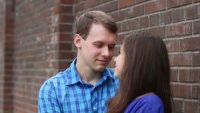 Ο άνδρας και η γυναίκα εξετάζουν ο ένας τον άλλον και το φιλί κοντά στο τουβλότοιχο απόθεμα βίντεο