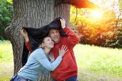Ο άνδρας και η γυναίκα κοντά σε μια βαλανιδιά κρύβουν από μια βροχή στη θερινή ημέρα Στοκ φωτογραφίες με δικαίωμα ελεύθερης χρήσης