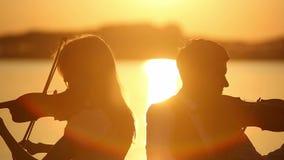 Ο άνδρας και η γυναίκα ντουέτου βιολιών παίζουν το βιολί στη φύση στο ηλιοβασίλεμα στη λίμνη φιλμ μικρού μήκους