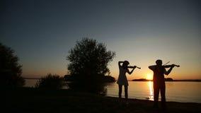 Ο άνδρας και η γυναίκα ντουέτου βιολιών παίζουν το βιολί στη φύση στο ηλιοβασίλεμα στη λίμνη απόθεμα βίντεο