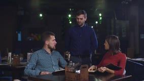 Ο άνδρας και η γυναίκα στο σερβιτόρο εστιατορίων φέρνουν την κάρτα και τα τρόφιμα διαταγής απόθεμα βίντεο