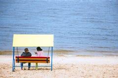 Ο άνδρας και μια γυναίκα κάθονται στην τράπεζα Στοκ εικόνα με δικαίωμα ελεύθερης χρήσης