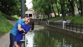 Ο άνδρας κλίνει πέρα από τη γυναίκα και φιλά τον κοντινό μικρό ποταμό της στο πάρκο απόθεμα βίντεο