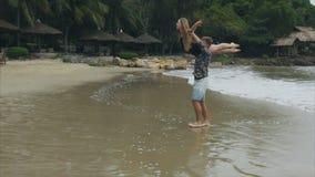 Ο άνδρας περιστρέφει μια γυναίκα στους ώμους του, νέος ερωτευμένος να στροβιλιστεί ζευγών σε μια παραλία θάλασσας Η έννοια μιας ε φιλμ μικρού μήκους
